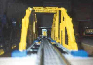 Looking down the yellow arch bridge as a locomotive starts across.